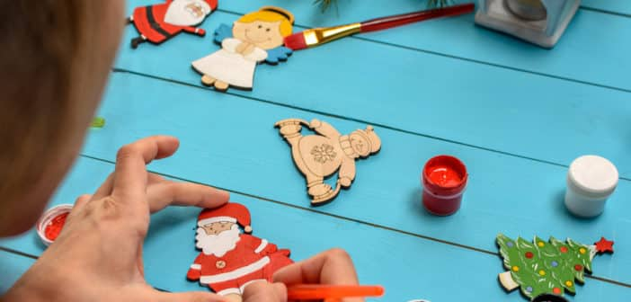 The boy with mum decorates by paints handmade wooden Christmas decorations on blue vintage table with a Christmas tree and toys